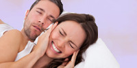 woman plugging ears while man snores